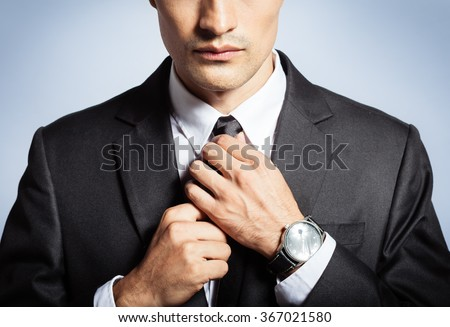 Man fixing his tie.  - stock photo