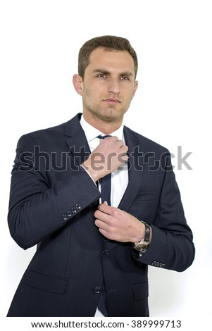 Man fixing his tie. Professional businessman in a white background