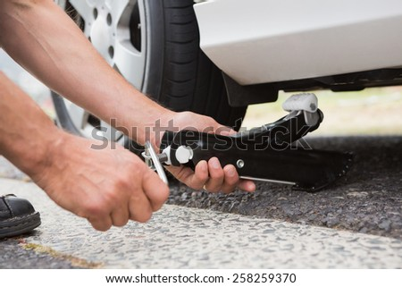 Man fixing tire of his car - stock photo
