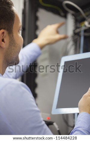 Man fixing wires with tablet pc in data center - stock photo