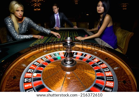 Man flanked by women, gambling at roulette table, portrait - stock photo