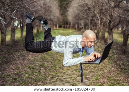 Man flies and works for laptop. - stock photo