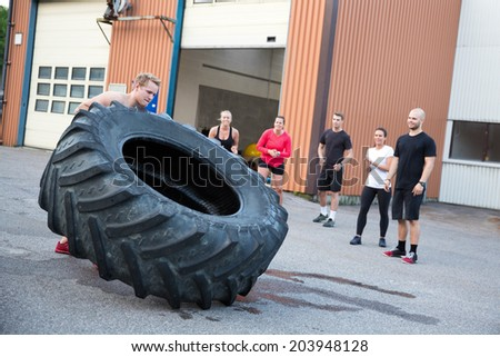 Man flipping heavy tires outdoor as workout - stock photo