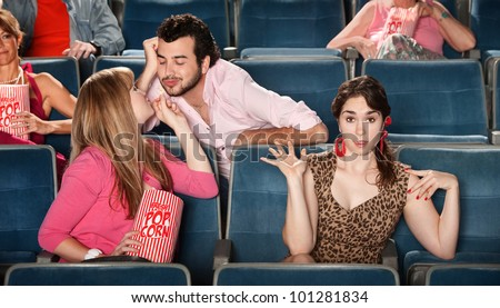 Man flirting with girl next to embarrassed friend in theater - stock photo