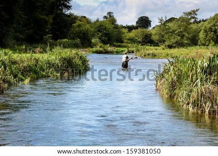 Man fly fishing casts on Irish river - stock photo