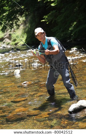 Man fly fishing in river - stock photo