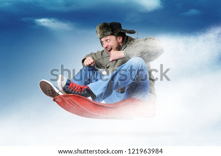 Man flying on a sleigh, concept festive sledging - stock photo