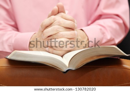man folded his hands in prayer on the Bible - stock photo