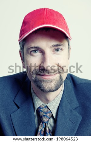 Man formally dressed and groomed with red cap.