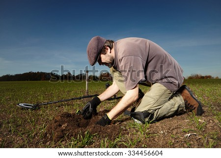 Man found on autumn field his treasure - stock photo