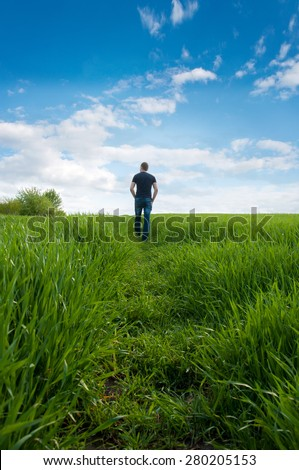 Man from the back on a long country path. Green field in the summer