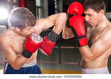 Man from the left is blocking the blow of another man