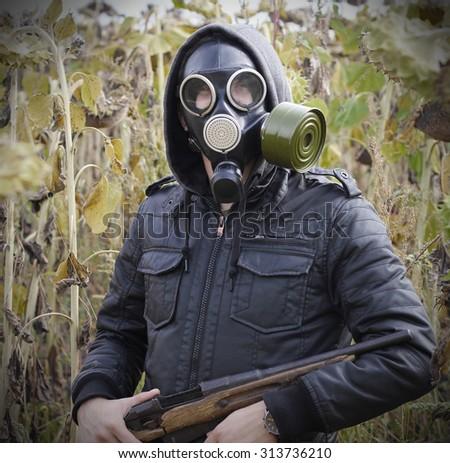 man gas mask gun concept the danger of war - stock photo