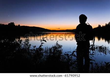 Man gazing out at the night sky shortly after sunset. - stock photo