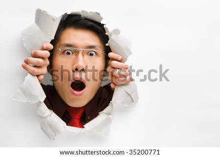 Man gazing surprisingly from hole in wall with copy space in horizontal position - stock photo