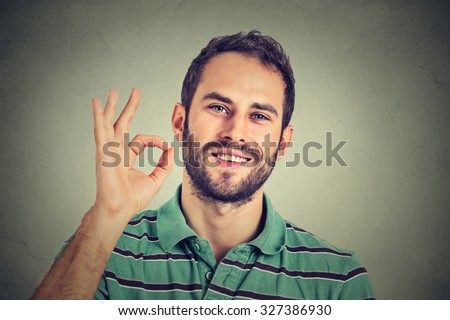 man gesturing OK sign isolated on gray wall background - stock photo