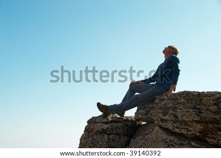 Man gesturing on the rock with blue background - stock photo