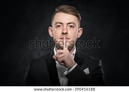 Man gesturing silent on a dark background. - stock photo