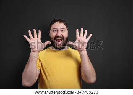 Man gesturing with hands and fingers spread open in front of a dark chalkboard