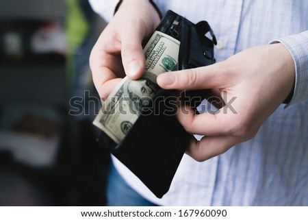 Man gets $ 100 from her purse - stock photo