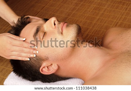 Man getting a facial / face massage at day spa - stock photo