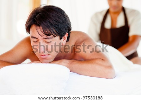 Man getting a massage on his body at the spa - stock photo