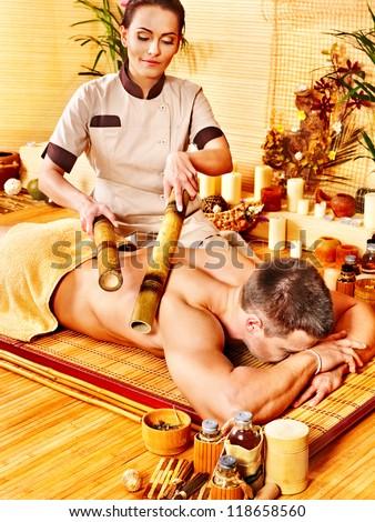 Man getting bamboo massage. Female therapist. - stock photo