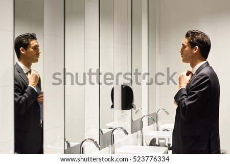 Man getting dressed in a public restroom with mirror. Businessman wearing suit and tie.