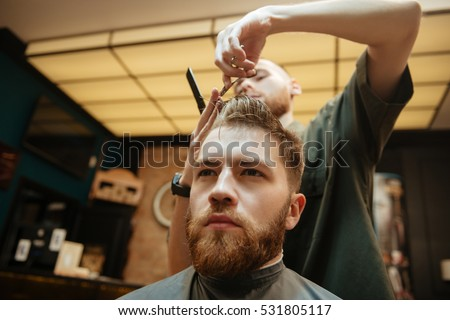 Man getting haircut by hairdresser with scissors while sitting in chair. Look aside.