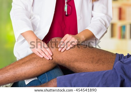 Man getting knee treatment from physio therapist, her hands holding his leg and applying massage, injury medical concept - stock photo