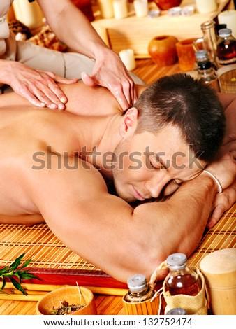 Man getting massage in bamboo spa. Female therapist. - stock photo