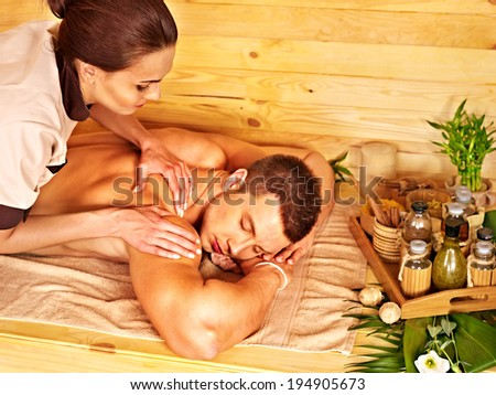 Man getting massage in bamboo spa. Female therapist.