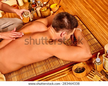 Man getting massage  on wooden floor in bamboo spa. Female therapist.