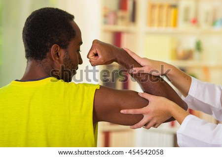 Man getting physical arm treatment from physio therapist, her hands working on his shoulder and elbow, medical concept - stock photo