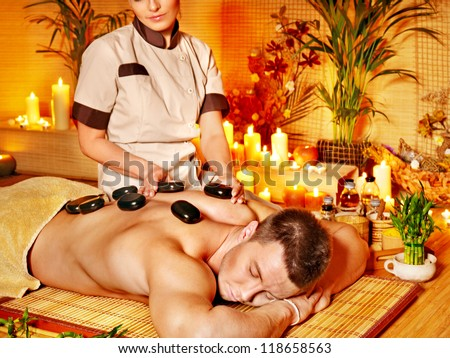 Man getting stone therapy massage in bamboo spa.