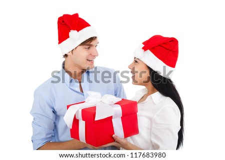 man give present gift box to smile woman, christmas holiday excited happy couple love smiling looking to each other, face to face, wear red new year hat cap, isolated over white background - stock photo