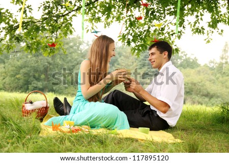 man gives a woman a gift on a picnic - stock photo