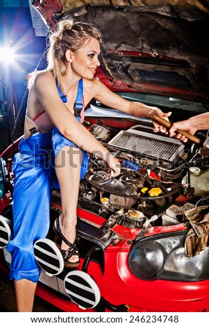 Man gives girl a tool to repair a car, working on the transmission. - stock photo