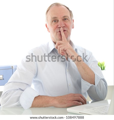 Man giving a shushing gesture with his finger Man giving a shushing gesture with his finger raised to his lips as he requests silence and quiet