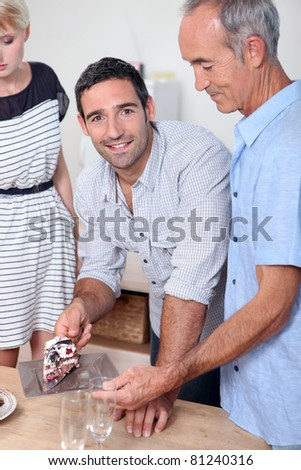 Man giving a slice of cake to his father - stock photo