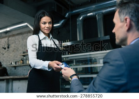 Man giving bank card to female waiter in restaurant