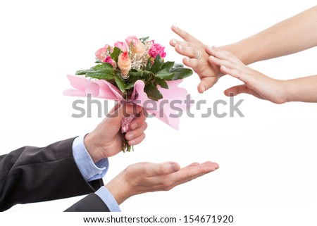 Man giving flowers to his wife after argument, isolated background - stock photo