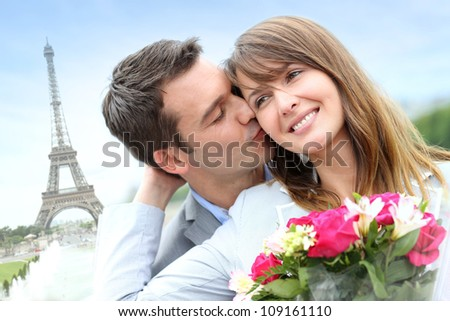 Man giving flowers to woman in Paris by the Eiffel Tower - stock photo