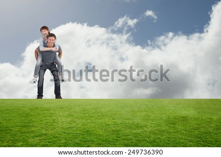 Man giving girl a piggy back against bright blue sky with clouds - stock photo