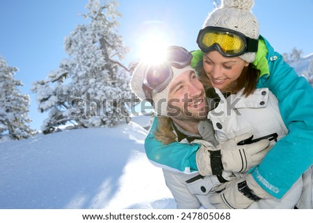 Man giving girlfriend piggyback ride in the snowy mountain - stock photo