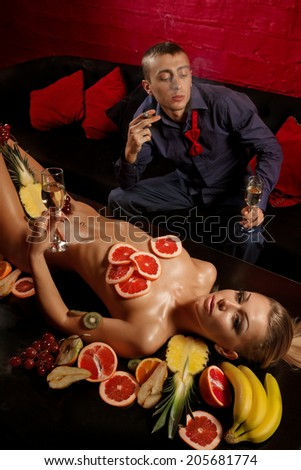 Man giving glass of champagne to naked woman decorated  by fruits  - stock photo