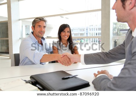 Man giving handshake to real-estate-agent - stock photo