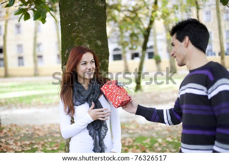 man giving her girlfriend a valentine day present (selective focus with shallow DOF)