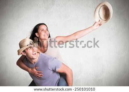 Man giving his pretty girlfriend a piggy back against white background - stock photo