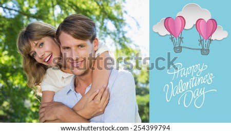 Man giving his pretty girlfriend a piggy back in the park smiling at camera against cute valentines message - stock photo